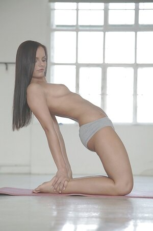 Slender brunette with sexy long legs and face practices sports topless