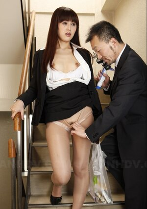 Fella in a suit takes off Asian's nylons on the stairs and aims strange toy at it