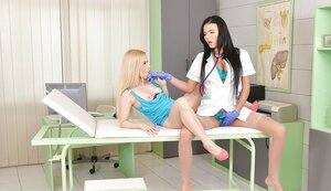 Youthful woman with blonde hair is licked by brunette doctor in blue gloves