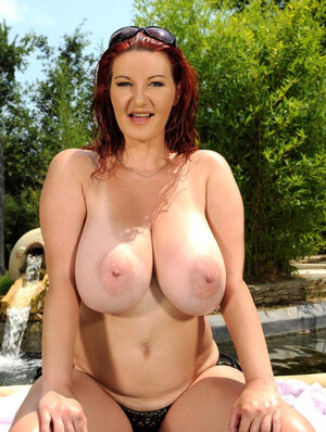 Temptress with red hair has fun with large breasts exposing them by the pool